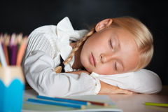 Tired school girl sleeping during lesson royalty free stock photo