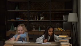 Tired school girls studying with a pile of books stock video