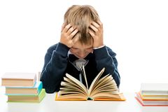 Tired schoolboy with books sitting at table. Portrait isolated Royalty Free Stock Photo