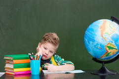 Tired schoolboy in classroom.  Royalty Free Stock Photo