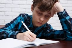 Tired schoolboy falling asleep while studying at copybook. Study. Ing difficulties, education, homework concept royalty free stock photography