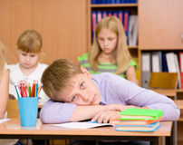 Tired schoolboy at a lesson at school Stock Photography