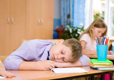 Tired schoolboy at a lesson at school Stock Image