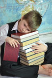 Tired schoolboy with a pile of books Stock Images