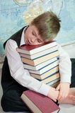 Tired schoolboy with a pile of books Royalty Free Stock Photo