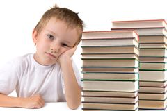 Tired schoolboy sits at the table Royalty Free Stock Images