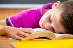 Tired schoolboy sleeping on book Stock Photography