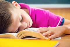 Tired schoolboy sleeping on book. In classroom Royalty Free Stock Photos