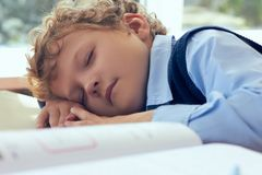 Tired Caucasian schoolboy sleeping in classroom at school. Сoncept of heavy workload in school. Tired schoolboy sleeping in classroom at school. Сoncept of Stock Photos