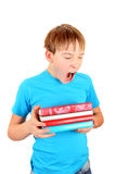 Tired Schoolboy yawning. Schoolboy with the Books Yawning Isolated on the White Background Stock Image
