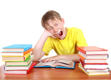 Tired Schoolboy yawning. Tired Kid Yawning at the School Desk with a Books on the white background Royalty Free Stock Photography