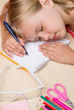Tired of schoolgirl asleep on the desk Stock Photography