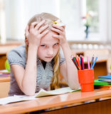 Tired schoolgirl in classroom. looking at camera Stock Image
