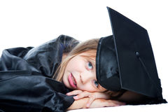 Tired schoolgirl in graduation dress on isolated w Stock Image