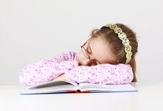 Tired schoolgirl sleeping on book stock image