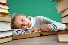 Tired schoolgirl sleeping on book. Photo of little girl in school around books. Education concept stock images