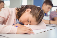 Tired schoolgirl sleeping in classroom Stock Images