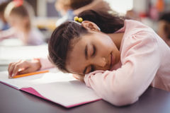 Tired schoolgirl sleeping in classroom. At school Royalty Free Stock Image