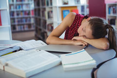 Tired schoolgirl sleeping while studying in library Royalty Free Stock Image