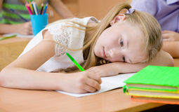Tired schoolgirl spoils the eyesight during the exam Royalty Free Stock Image
