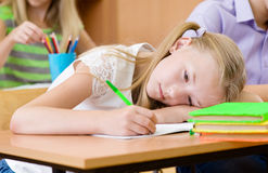 Tired schoolgirl spoils the eyesight during the exam Royalty Free Stock Photo