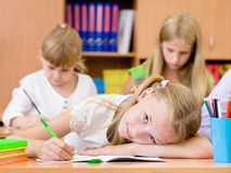 Tired schoolgirl writes in a notebook during lesson Royalty Free Stock Images