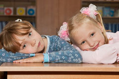 Tired schoolgirls lie on the desk Stock Photo