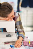 Tired seamstress sleeping on sewing machine Stock Photography