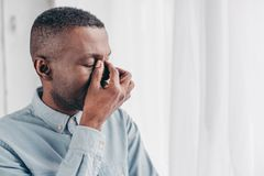 Tired senior african american man. Rubbing bridge of nose stock image