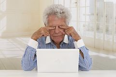 Tired Senior Businessman in front of laptop Stock Photos