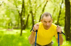 Tired senior man making nordic walking in the park.  royalty free stock photography