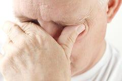 Tired Senior Man Rubs Eyes Stock Images