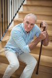 Tired senior man sitting on stairs. Portrait of tired senior man sitting on stairs at home Stock Photos