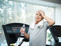 Tired senior man on a treadmill Stock Photos