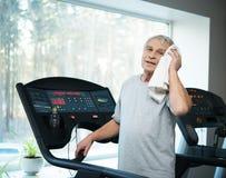 Tired senior man on a treadmill stock photography