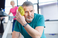 Tired senior sportsman resting, sportswoman on treadmill behind royalty free stock images