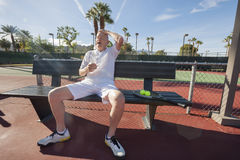 Tired senior tennis player relaxing on bench at court Royalty Free Stock Photos