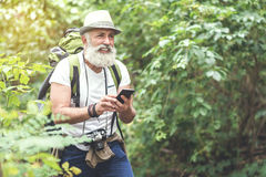 Tired senior tourist searching place of destination with phone. Portrait of exhausted old man looking for location while hiking in forest. He is using navigator Royalty Free Stock Photography