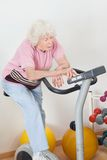 Tired Senior Woman Exercising On Bike Royalty Free Stock Photography