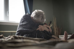 Tired senior woman on her bed Royalty Free Stock Images