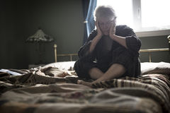 Tired senior woman on her bed Royalty Free Stock Photo