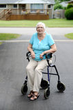 Tired senior woman sitting on walker Stock Photo