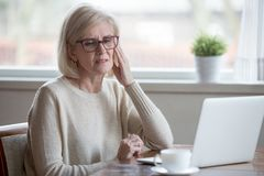 Tired senior woman suffering from headache working at laptop. Upset aged woman using laptop at home suffering from headache, tired senior female massaging stock photos
