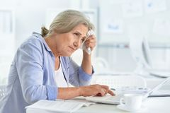 Tired senior woman using laptop. At office Stock Image