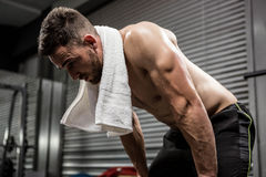 Tired shirtless man with towel around neck. At the crossfit gym stock image