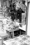 Tired Shop Keeper India. A black and white image of a yawning shop keeper in a market general store in Rishikesh India is surrounded by products royalty free stock image