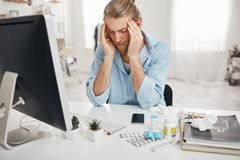 Sick Caucasian man sitting at office, squeezing temples because of headache, working on computer, looking at the screen. Tired sick Caucasian man sitting at royalty free stock photo