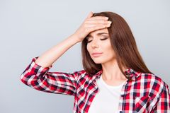 Tired sick pretty brown haired young lady with sad grimace. She. Is holding the forehead, wearing the checkered shirt, standing on pure background Stock Images