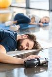 Tired sleeping man lying on mat. Tired sleeping men lying on mat at gym Stock Image