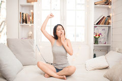Tired sleepy asian woman waking up and stretching while sitting Royalty Free Stock Photo